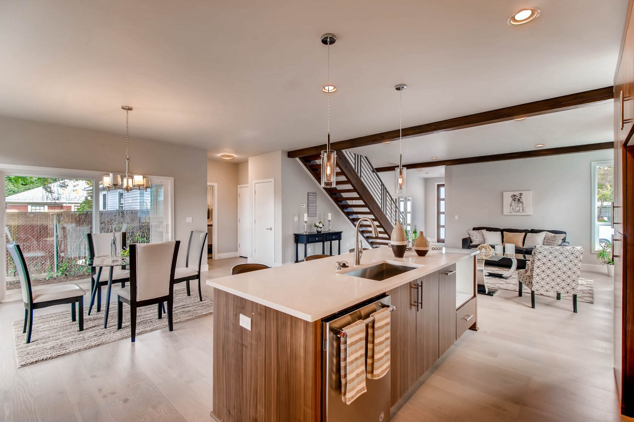 Open concept, modern remodel with view of the dining and sitting areas, stairwell, and kitchen island