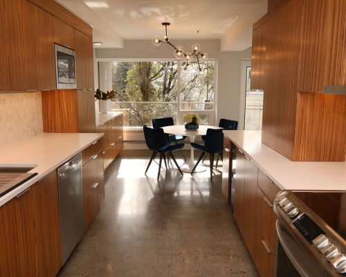 Kitchen with striped natural wood cabinets, white counters, stainless steel appliances, and a view of the dining area in this recent condo remodel