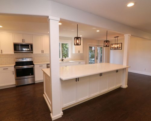 Kitchen with dark floors, white cabinetry and counters in a custom full-home remodel
