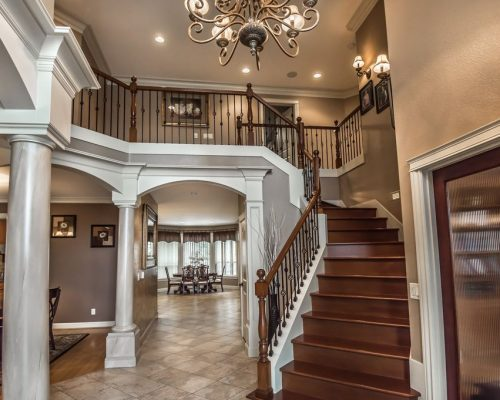 Pillars, moulding, stairwell, and view into the dining room in this luxury custom built home