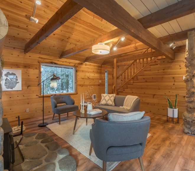 Sitting area at the bottom of a staircase, near a stone fireplace with a smoothed log mantle in a remodeled log cabin retreat