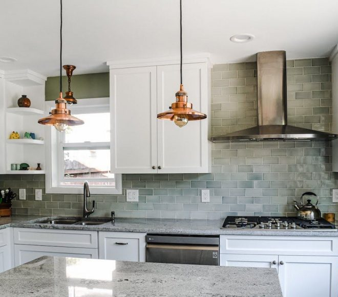 Kitchen with white cabinetry, gray/white speckled marble counters, and stainless steel appliances in a recently remodeled home