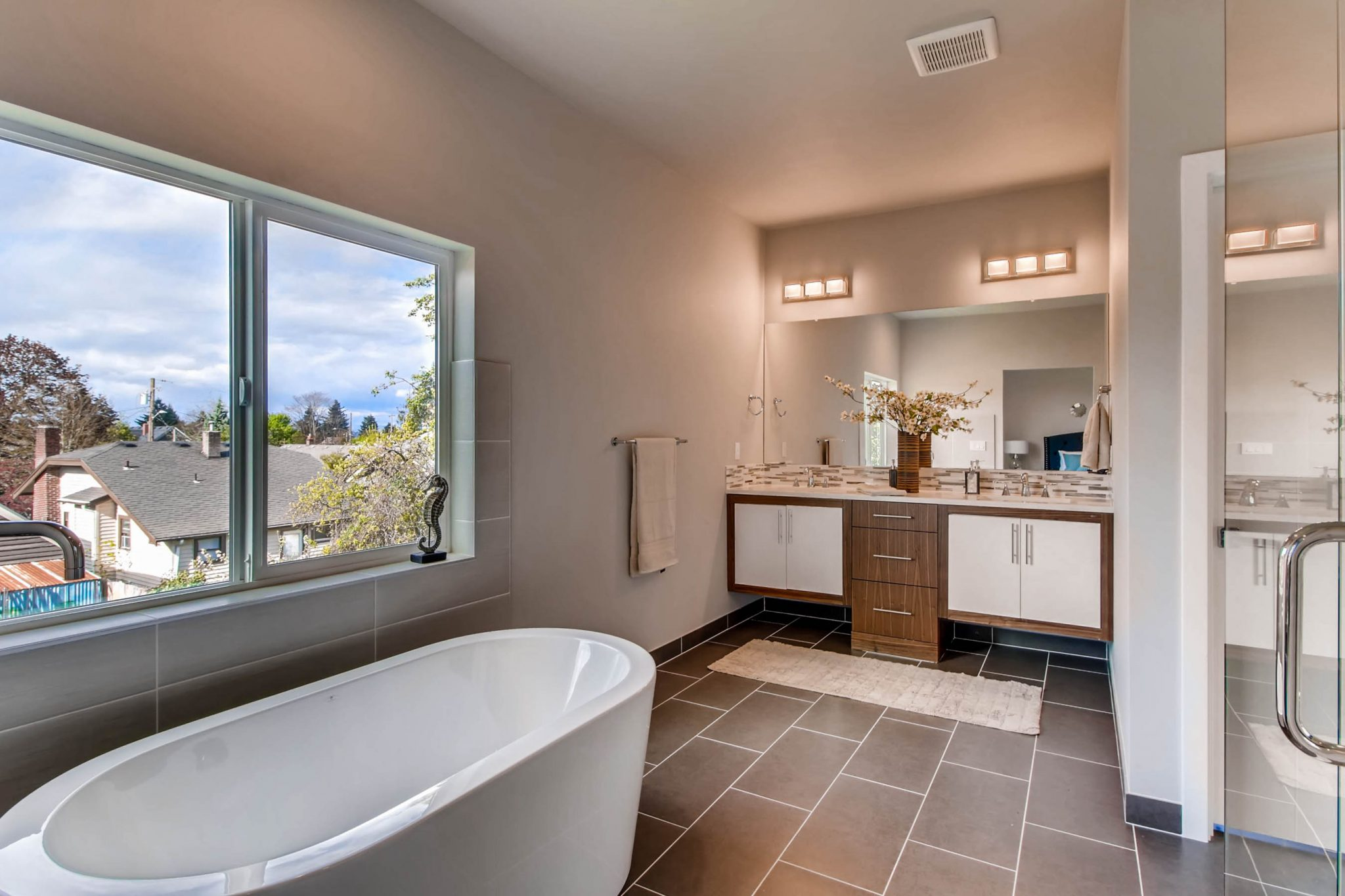 Bathroom with white cabinetry and counters in a luxury home remodel