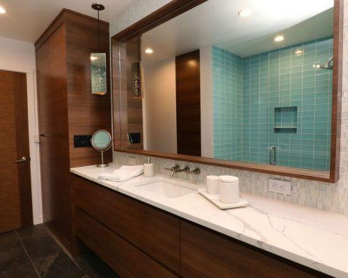 Modern bathroom remodel with in-set mirror framed by dark wood