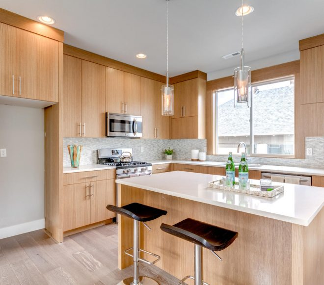 Kitchen with natural wood cabinetry, white counters, and stainless steel appliances in a modern duplex remodel