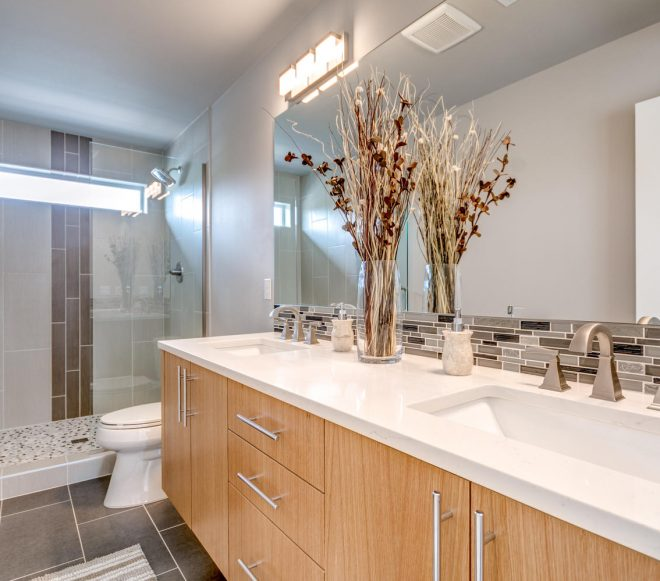 Master bathroom with titled walk-in shower, side-by-side basins, and stainless fixtures in a modern duplex remodel
