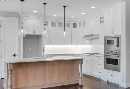 Custom remodeled kitchen with white cabinetry, gray accented marble counters, and stainless steel appliances in a modern ranch house