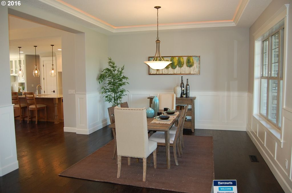 Remodeled dining room with dark wood floors and large windows in a remodeled modern ranch house