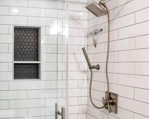 Walk-in shower with white tile walls and stainless fixtures