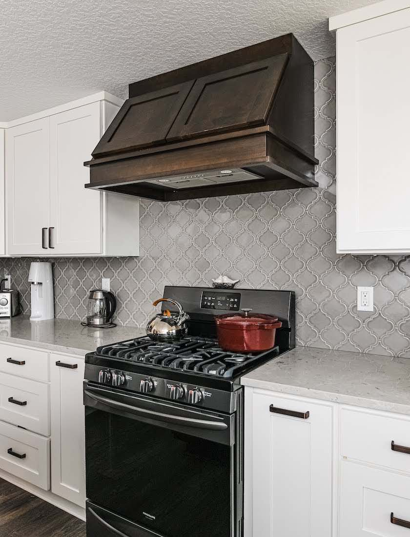Kitchen with natural wood hood vent, white cabinetry, gray accented white marble counters, and black appliances in a recently remodeled home