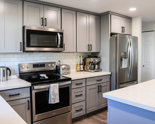 Kitchen remodel featuring stainless steel appliances, custom gray cabinetry, and white marble counters