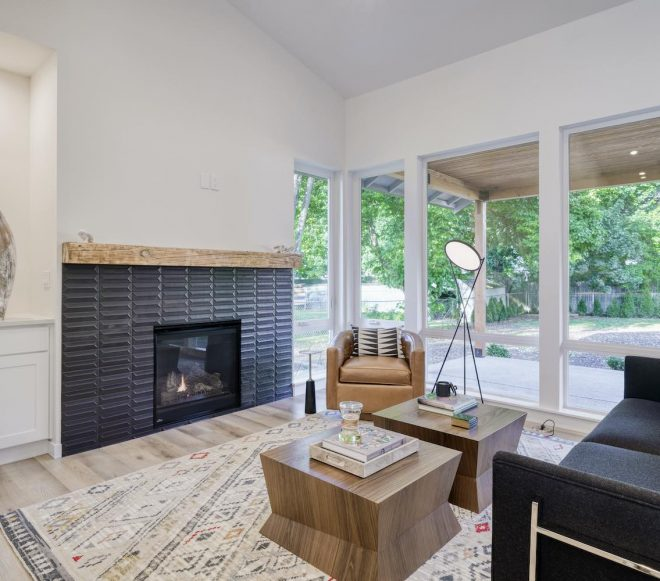 Living room remodel featuring build-in cabinets, light wood floors, and large bay windows